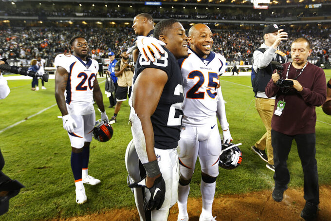 Oakland Raiders running back Josh Jacobs stands with Denver Broncos cornerback Chris Harris (25) at the end of an NFL football game Monday, Sept. 9, 2019, in Oakland, Calif. Oakland won the game 24-16. In the background is Denver Broncos defensive back Duke Dawson (20). (AP Photo/D. Ross Cameron)