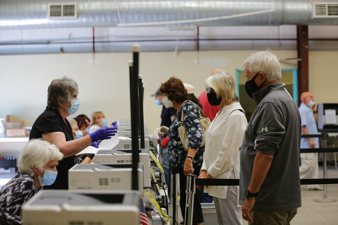 Poll workers help voters behind plastic barriers during primary voting on Tuesday, June 2, 2020, in Santa Fe, New Mexico. In the county's first election since the COVID-19 pandemic took hold, poll workers wore surgical masks and voters were given a squirt of hand sanitizer as they entered the building, a warehouse next to the county's rodeo grounds. (AP Photo/Cedar Attanasio)