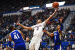 Connecticut's James Bouknight, center, reaches to keep the ball in play as Tulsa's Jeriah Horne, left, and Elijah Joiner, right, defend in the first half of an NCAA college basketball game, Sunday, Jan. 26, 2020, in Hartford, Conn. (AP Photo/Jessica Hill)