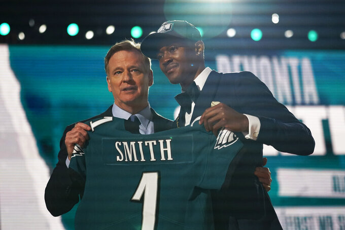 Alabama wide receiver DeVonta Smith, right, holds a team jersey with NFL Commissioner Roger Goodell after he was chosen by the Philadelphia Eagles with the 10th pick in the first round of the NFL football draft Thursday, April 29, 2021, in Cleveland. (AP Photo/Tony Dejak)