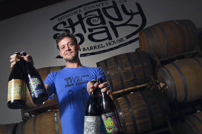 "In this Feb. 29, 2016 photo, Steve Doty, owner of Shady Oak Barrel House, poses for photos in Santa Rosa, Calif. Anger over devastating California wildfires sparked by Pacific Gas & Electric power lines is coming to a head — in a beer. And an outcry is brewing. Doty a new beer called ""F--- PG&E,"" describing it on Facebook last week as ""a classic California pale ale, featuring Cashmere and Simcoe hops and a touch of malt sweetness."" (Christopher Chung/The Press Democrat via AP)"