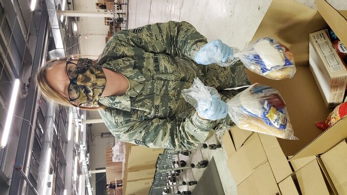 In a photo provided by Project Isaiah, a member of the Michigan National Guard helps to sort food for distribution in Detroit on Friday, May 1, 2020 as part of the Project Isaiah relief effort bringing thousands of prepackaged meals to COVID-positive residents in the city. (Project Isaiah via AP)