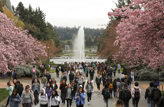 FILE - In this April 3, 2019, file photo, students walk between classes on the University of Washington campus in Seattle. Five Black police officers claiming racism at the University of Washington have filed claims for $8 million in damages. They say they were routinely insulted and demeaned by co-workers and supervisors. KOMO-TV reported Tuesday, June 22, 2021, that the officers say they were disciplined and denied promotions because of their race. (AP Photo/Ted S. Warren, File)