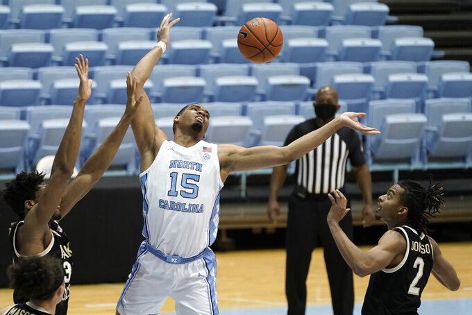 North Carolina forward Garrison Brooks (15) reaches for a rebound with Wake Forest center Emmanuel Okpomo, left, and guard Jalen Johnson (2) during the first half of an NCAA college basketball game in Chapel Hill, N.C., Wednesday, Jan. 20, 2021. (AP Photo/Gerry Broome)