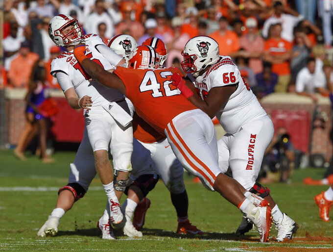 North Carolina State quarterback Ryan Finley (15) is pressured by Clemson's Christian Wilkins (42) while Joshua Fedd-Jackson (66) tries to block during the first half of an NCAA college football game Saturday, Oct. 20, 2018, in Clemson, S.C. (AP Photo/Richard Shiro)
