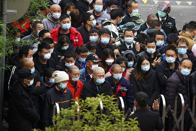 An officer, foreground, talks to the masked workers gather at the parking lot entrance gate to wait for the COVID-19 test at the Shanghai Pudong International Airport in Shanghai, Monday, Nov. 23, 2020. Chinese authorities are testing millions of people, imposing lockdowns and shutting down schools after multiple locally transmitted coronavirus cases were discovered in three cities across the country last week. (AP Photo)