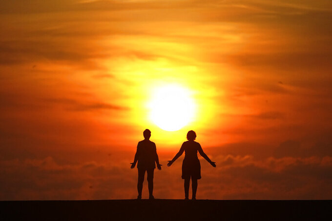 FILE - In this Sept. 19, 2020 file photo, a couple greets the sun as they stand on a jetty while the sun rises over the Atlantic Ocean, in Bal Harbour, Fla. Even when they firmly believe in gender equality, many opposite-sex couples struggle to remain truly equal in their partnership, especially once children are in the picture. While couples may have the best of intentions, implicit bias can make them repeat patterns that don't serve their relationship.  (AP Photo/Wilfredo Lee, File)