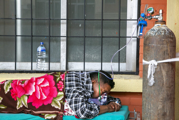 A COVID-19 patient receives oxygen as he lies on a bed outside an emergency ward of a government run hospital in Kathmandu, Nepal, Friday, May 7, 2021. Across the border from a devastating surge in India, doctors in Nepal warned Friday of a major crisis as daily coronavirus cases hit a record and hospitals were running out of beds and oxygen. (AP Photo/Niranjan Shrestha)