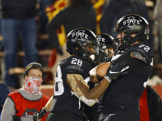 Iowa State running back Breece Hall, left, celebrates his touchdown with offensive lineman Jake Remsburg, right, during the second half of an NCAA college football game against West Virginia on Saturday, Dec. 5, 2020, in Ames, Iowa. (AP Photo/Matthew Putney)