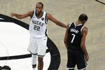 Milwaukee Bucks' Khris Middleton (22) calls to teammates after Brooklyn Nets' Kevin Durant (7) missed a shot during overtime of Game 7 of a second-round NBA basketball playoff series Saturday, June 19, 2021, in New York. (AP Photo/Frank Franklin II)