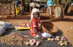 In this Wednesday, May 13, 2020, photo, a child sits on the ground selling onions at a market stall in Tougan, Burkina Faso. Violence linked to Islamic extremists has spread to Burkina Faso's breadbasket region, pushing thousands of people toward hunger and threatening to cut off food aid for millions more. (AP Photo/Sam Mednick)