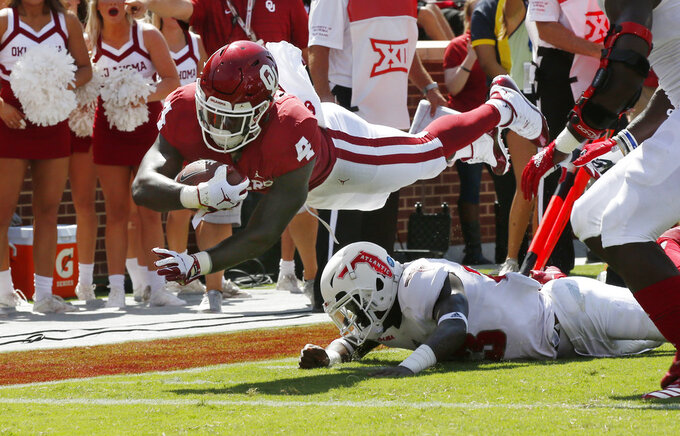 FILE - In this Saturday, Sept. 1, 2018 file photo, Oklahoma running back Trey Sermon (4) dives over Florida Atlantic safety James Pierre (23) for a touchdown in the first half of an NCAA college football game in Norman, Okla. Oklahoma lost star Rodney Anderson for the season to a right knee injury against UCLA over the weekend. Sermon is one of the top backs left in the rotation. (AP Photo/Sue Ogrocki, File)