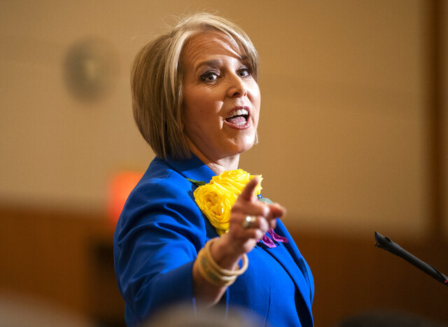 FILE - In this Jan. 21, 2020, file photo New Mexico Gov. Michelle Lujan Grisham gives her State of the State address during the opening of the New Mexico legislative session in the House chambers at the state Capitol in Santa Fe, N.M. In the presidential primary, Joe Biden is likely to receive a warm welcome among most Democrats in New Mexico, where Grisham has pledged to help Biden connect with racial- and ethnic-minority voters.   (AP Photo/Craig Fritz, File)