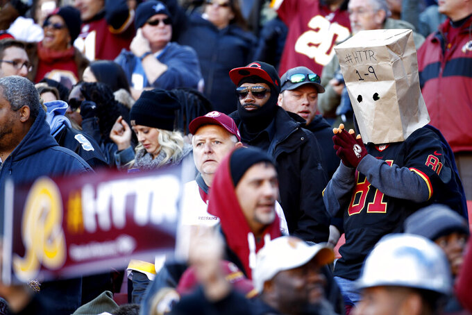 A spectator wears a paper bag on his head while watching the first half of an NFL football game between the Washington Redskins and the Detroit Lions, Sunday, Nov. 24, 2019, in Landover, Md. (AP Photo/Patrick Semansky)