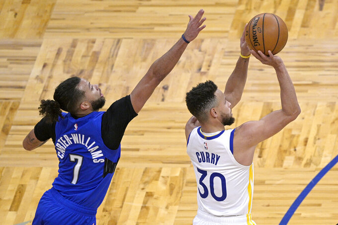 Golden State Warriors guard Stephen Curry (30) goes up for a shot in front of Orlando Magic guard Michael Carter-Williams (7) during the first half of an NBA basketball game, Friday, Feb. 19, 2021, in Orlando, Fla. (AP Photo/Phelan M. Ebenhack)