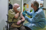 A doctor inoculates Herri Rehfeld, 92, against the new coronavirus with the Pfizer/BioNTech vaccine at the vaccination center at the Messe Berlin trade fair grounds on the center's opening day in Berlin, Germany, Monday, Jan. 18, 2021. The center is the third to open in Berlin. Three more are to open in coming weeks once shipments of the Pfizer/BioNTech and Moderna vaccines pick up pace. (Sean Gallup/Getty Images via AP, Pool)