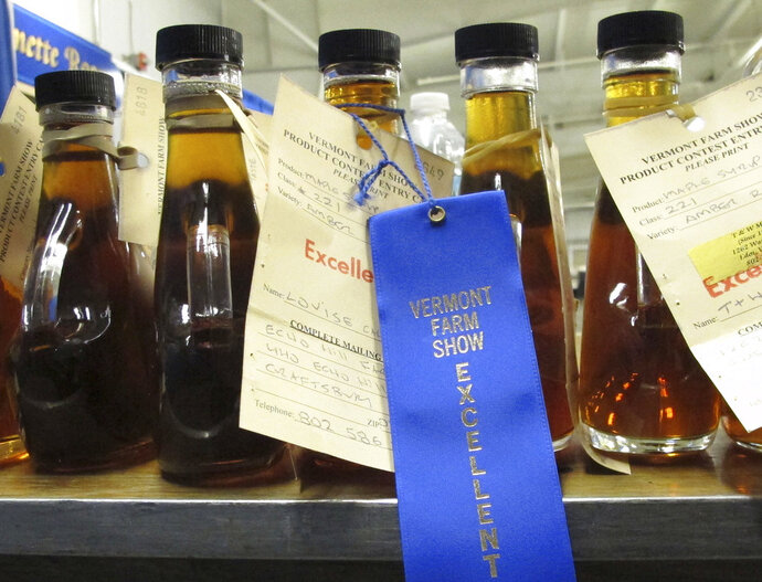 In this Monday, Jan. 29, 2018 photo, maple syrup entries rated as excellent sit on a table at the Vermont Farm Show in Essex Junction, Vt. Each year a panel of judges rates the entries in the state that is the largest producer of maple syrup. (AP Photo/Lisa Rathke)