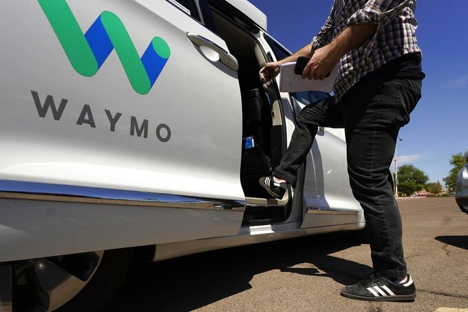 FILE - In this April 7, 2021 file photo, a Waymo minivan arrives to pick up passengers for an autonomous vehicle ride, in Mesa, Ariz. Waymo, the self-driving car pioneer spun off from Google, isn't allowing a recent wave of executive departures to detour its plans to expand its robotic taxi service. The Mountain View, Calif., company made that clear Wednesday, June 16 by announcing it has raised another $2.5 billion from a group of investors ranging from venture capital firms such as Andreessen Horowitz to a major car dealer, AutoNation. (AP Photo/Ross D. Franklin, File)