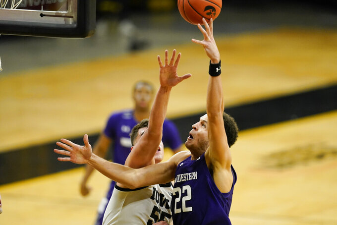 Northwestern forward Pete Nance (22) drives to the basket past Iowa center Luka Garza during the first half of an NCAA college basketball game, Tuesday, Dec. 29, 2020, in Iowa City, Iowa. (AP Photo/Charlie Neibergall)