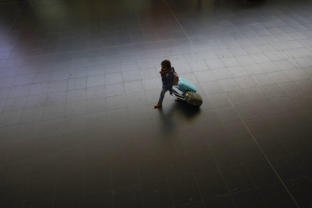 A passenger carries her luggage through an almost empty Termini main train station, in Rome, Monday, March 23, 2020. For most people, the new coronavirus causes only mild or moderate symptoms. For some it can cause more severe illness, especially in older adults and people with existing health problems.(AP Photo/Andrew Medichini)