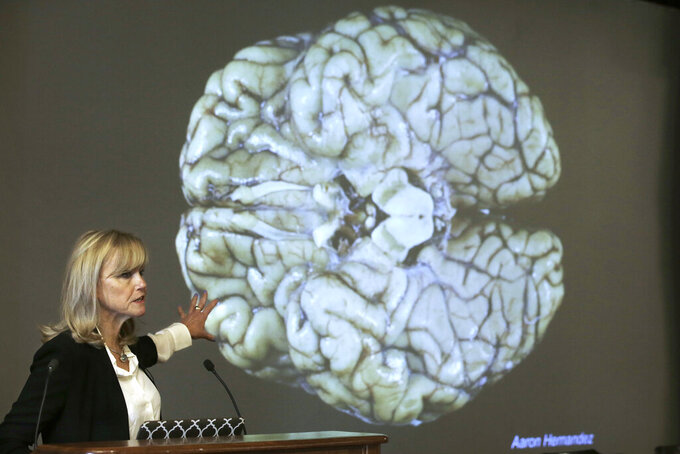 FILE - In this Thursday, Nov. 9, 2017 file photo, Ann McKee, director Boston University's center for research into the degenerative brain disease chronic traumatic encephalopathy, or CTE, addresses an audience on the school's campus about the study of NFL football player Aaron Hernandez's brain, projected on a screen behind in Boston. According to a new public service announcement, signing a pre-teen child up for tackle football is like teaching him to smoke. The ad from the Concussion Legacy Foundation encourages parents to choose flag football for children younger than 14.  (AP Photo/Steven Senne, File)