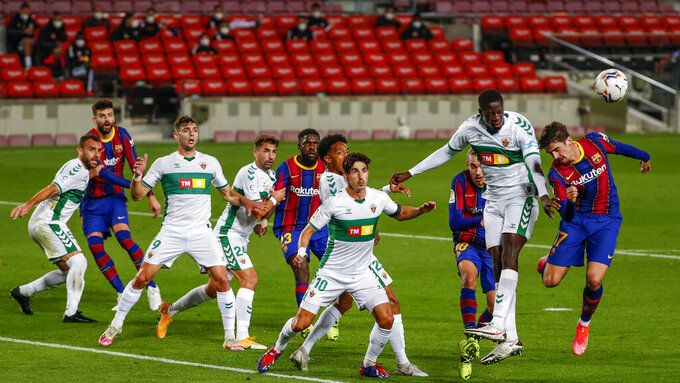 Barcelona's Francisco Trincao, right, and Elche's Omenuke Mfulum second right, jump for the ball during the Spanish La Liga soccer match between FC Barcelona and Elche at the Camp Nou stadium in Barcelona, Spain, Wednesday, Feb. 24, 2021. (AP Photo/Joan Monfort)