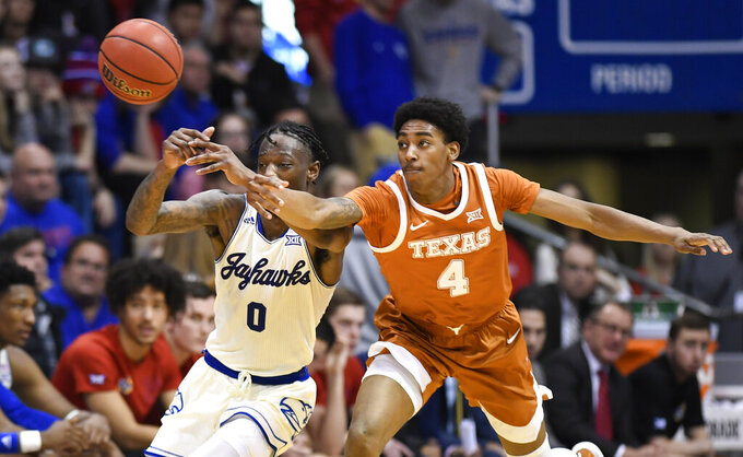 Texas guard Donovan Williams (4) steals the ball from Kansas guard Marcus Garrett (0) during the second half of an NCAA college basketball game in Lawrence, Kan., Monday, Feb. 3, 2020. (AP Photo/Reed Hoffmann)
