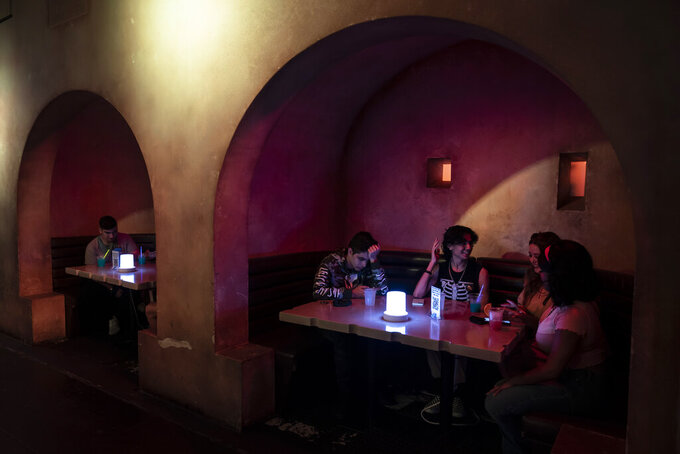 Customers chat at Scum and Villainy Cantina, a bar located on Hollywood Blvd, in Los Angeles, Tuesday, May 4, 2021. California has the lowest infection rate in the country. Los Angeles County, which is home to a quarter of the state's nearly 40 million people and has endured a disproportionate number of the state's 60,000 deaths, didn't record a single COVID-19 death Sunday or Monday, which was likely due to incomplete weekend reporting but still noteworthy. (AP Photo/Jae C. Hong)