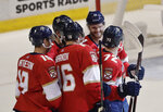 Florida Panthers left wing Jonathan Huberdeau, center, smiles at Florida Panthers center Frank Vatrano, right, along with his teammates after Vatrano score during the first period of an NHL hockey game against the Montreal Canadiens on Sunday, Feb. 17, 2019, in Sunrise, Fla. (AP Photo/Brynn Anderson)