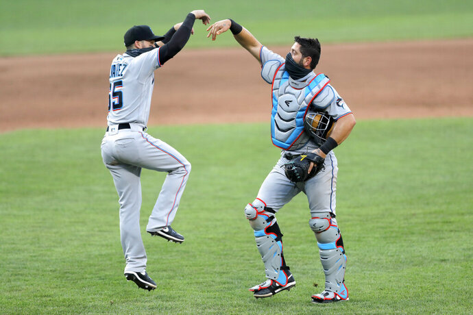 Miami Marlins catcher Francisco Cervelli, right, and second baseman Eddy Alvarez celebrate after defeating the Baltimore Orioles 1-0 during game one of a baseball double-header, Wednesday, Aug. 5, 2020, in Baltimore. (AP Photo/Julio Cortez)