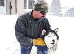 Mark Jones takes a break from clearing off his driveway with his dog Akai on Friday, Jan. 17, 2020, in Sioux Falls, S.D. Minnehaha County is currently under a winter storm warning and will be under a blizzard warning tonight. (Abigail Dollins/The Argus Leader via AP)