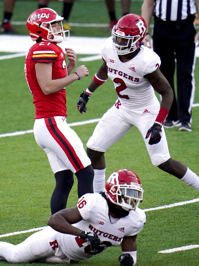 Maryland kicker Joseph Petrino, left, looks on as he misses a field goal as Rutgers' Avery Young (2) and defensive back Max Melton (16) react during overtime of an NCAA college football game, Saturday, Dec. 12, 2020, in College Park, Md. Rutgers won 27-24 in overtime. (AP Photo/Julio Cortez)