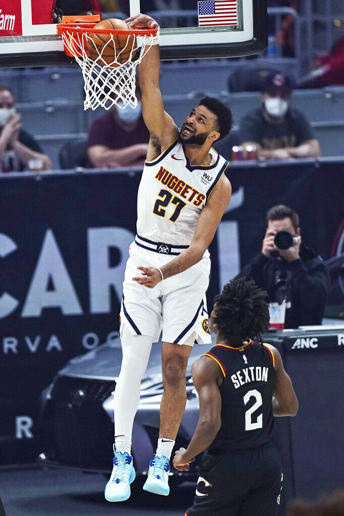 Denver Nuggets' Jamal Murray (27) dunks next to Cleveland Cavaliers' Collin Sexton (2) during the first half of an NBA basketball game Friday, Feb. 19, 2021, in Cleveland. (AP Photo/Tony Dejak)