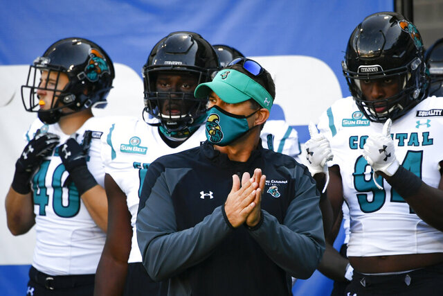 FILE - In this Oct. 31, 2020, file photo, Coastal Carolina coach Jamey Chadwell waits to lead his team onto the field for an NCAA football game against Georgia State in Atlanta. Chadwell is The Associated Press college football coach of the year after leading the Chanticleers to a surprising near-perfect season. Chadwell received 16 first-place votes and 88 points from the AP Top 25 panel to finish ahead of Indiana's Tom Allen, who was second with 14 first-place votes and 66 points. (AP Photo/John Amis, File)