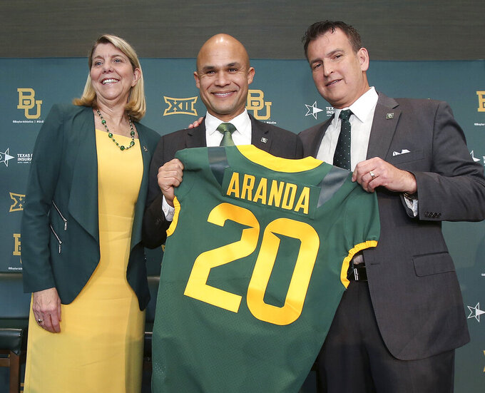 Baylor University President Dr. Linda A. Livingstone, left, and Athletic Director Mack Rhoades, right, present new head football coach Dave Aranda, center, with a jersey during an during an NCAA college football news conference, Monday, Jan. 20, 2020, in Waco, Texas. (Jerry Larson/Waco Tribune-Herald via AP)