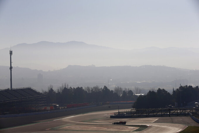 A lone car drives on the track during a Formula One pre-season testing session at the Barcelona Catalunya racetrack in Montmelo, outside Barcelona, Spain, Wednesday, Feb. 27, 2019. (AP Photo/Joan Monfort)