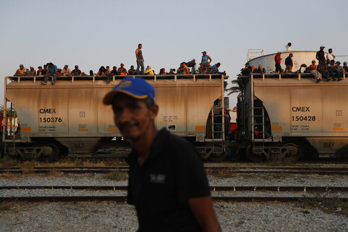 FILE - In this April 23, 2019 file photo, Central American migrants ride a freight train on their way to the U.S.-Mexico border, in Ixtepec, Oaxaca state, Mexico. Mexico President Andrés Manuel López Obrador said on Monday, May 20,2019 that U.S. support for economic development in Mexico and Central America is the best option for stemming the flow of immigrants, meanwhile the U.S. and Mexico are discussing an arrangement under which the U.S. government would guarantee some $10 billion in development investments for Mexico and Central America. (AP Photo/Moises Castillo, File)
