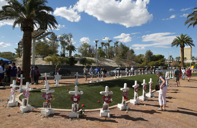 FILE - In this Sept. 30, 2018, file photo, people visit a makeshift memorial for victims of the Oct. 1, 2017, mass shooting in Las Vegas. A coroner in Southern California has attributed the death of a woman to wounds she received in the Las Vegas mass shooting in October 2017. The decision by authorities in San Bernardino County would add Kimberly May Gervais to the list of 58 people killed in the deadliest mass shooting in modern American history. (AP Photo/John Locher, File)