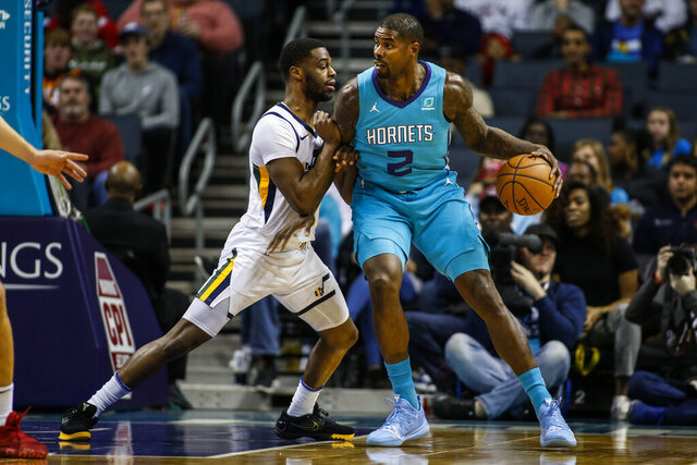 Charlotte Hornets forward Marvin Williams, right, drives into Utah Jazz guard Emmanuel Mudiay in the first half of an NBA basketball game in Charlotte, N.C., Saturday, Dec. 21, 2019. (AP Photo/Nell Redmond)