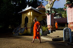 In this Nov. 17, 2019, photo, a Buddhist monk walk inside a temple in the early morning on the outskirts of Kandy, Sri Lanka. In this mountain city that was for centuries home to Sri Lanka's kings and in recent years has been riven by religious violence, Buddhist nationalists are rejoicing the election of the country's newest leader. They hope he ushers in another golden era for the nation's ethnic majority. Buddhist nationalism has been on the rise, and it was thrust to the forefront of Sri Lankan politics after Islamic State-inspired suicide attacks by local militants killed 269 people at churches and hotels on Easter Sunday. (AP Photo/Dar Yasin)