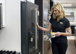 """In this March 11, 2018, photo provided by Mrs. G Inc., Debbie Schaeffer, owner of Mrs. G, an appliance retailer in Lawrence Township, N.J., poses for a photo at the GE Cafe Keurig Refrigerator display. A slowdown in home sales is creating opportunities for small businesses like home renovators and appliance dealers. """"People are confident and spending money and reinvesting in their homes,"""" Schaeffer said. (Ashlee Cain/Mrs. G Inc. via AP)"""
