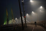 Street lamps on the Tilikum Crossing Bridge illuminate smoke from wildfires, Sunday, Sept. 13, 2020, in Portland, Ore. Smoke from burning wildfires has caused poor air quality in Portland and other cities along the West Coast. (AP Photo/John Locher)