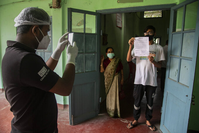 A health worker takes photograph of a person holding a document confirming he has tested positive for COVID-19 at a government run hospital in Gauhati, India, Saturday, May 8, 2021. Infections have swelled in India since February in a disastrous turn blamed on more contagious variants as well as government decisions to allow massive crowds to gather for religious festivals and political rallies. (AP Photo/Anupam Nath)