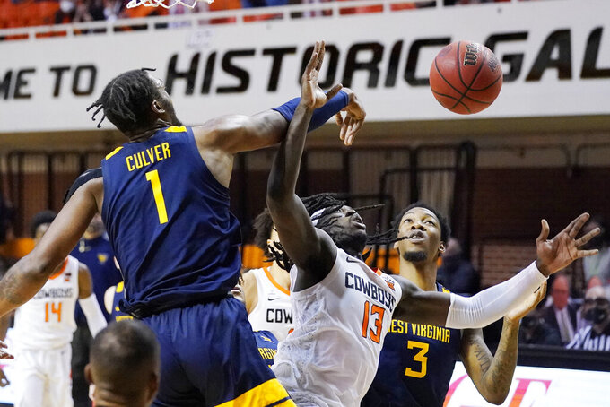 West Virginia forward Derek Culver (1) blocks a shot by Oklahoma State guard Isaac Likekele (13) in front of teammate Gabe Osabuohien (3) in the second half of an NCAA college basketball game Monday, Jan. 4, 2021, in Stillwater, Okla. (AP Photo/Sue Ogrocki)