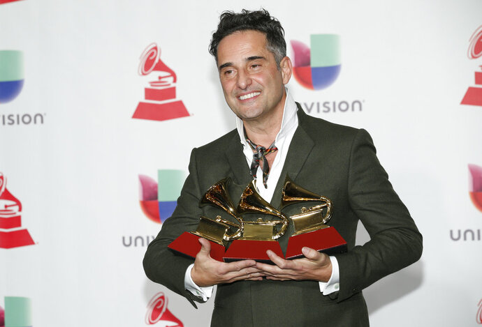 Jorge Drexler poses in the press room with the awards for best singer-songwriter album for