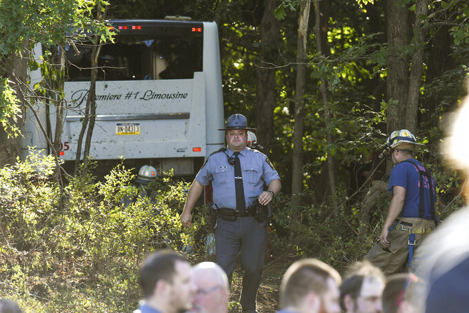 First responders work the scene after a Premiere #1 Limousinebus crashed into a wooded area off I-81 in Frailey Township, Pa., on Sunday, Sept. 19, 2021. The bus was traveling on I-81 south and came off the Hegins exit ramp, crossing through the divider on Rt. 25 and crashing into a wooded area off Rt. 25 where it came to a stop. (Jacqueline Dormer/Republican-Herald via AP)