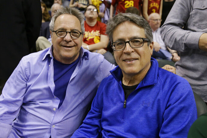 """FILE - In this March 15, 2016, file photo, """"Hoosiers"""" director David Anspaugh, left, and writer Angelo Pizzo pose during an NBA basketball game between the Indiana Pacers and the Boston Celtics in Indianapolis. """"Hoosiers"""" shot all the way to No. 1 in The Associated Press best sports movies Top 25. (AP Photo/Michael Conroy, File)"""