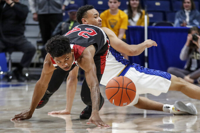 Northern Illinois's Darius Beane (24) tumbles over Pittsburgh's Trey McGowens as he chases a loose ball during the first half of an NCAA college basketball game, Monday, Dec. 16, 2019, in Pittsburgh. (AP Photo/Keith Srakocic)