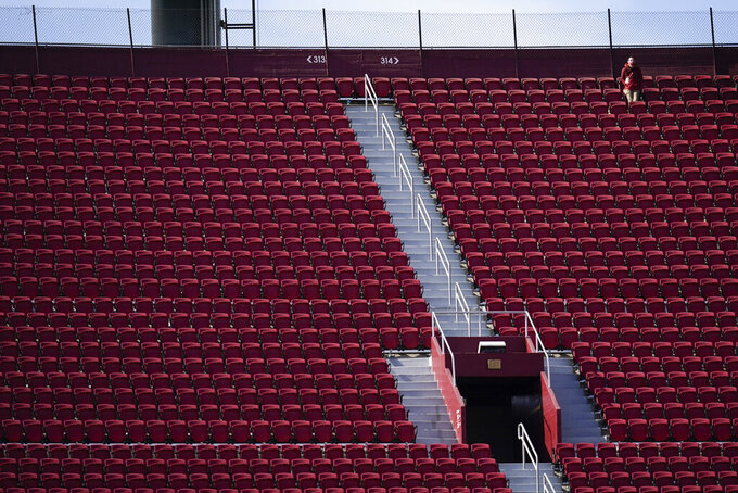 A man stands alone in the upper part of the stands during the second half of an NCAA college football game between Southern California and Arizona State, Saturday, Nov. 7, 2020, in Los Angeles. (AP Photo/Ashley Landis)