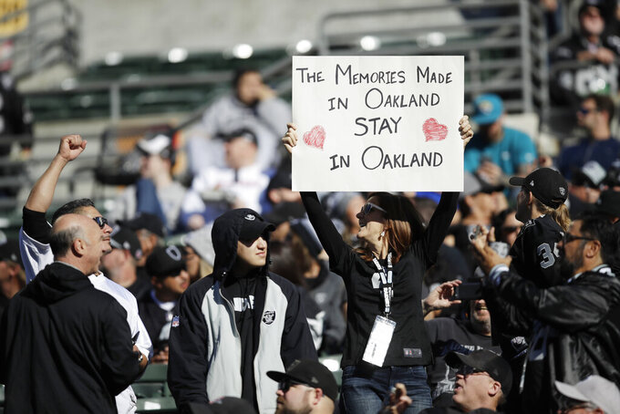 An Oakland Raiders fans holds up a sign during the first half of an NFL football game against the Jacksonville Jaguars in Oakland, Calif., Sunday, Dec. 15, 2019. (AP Photo/Ben Margot)